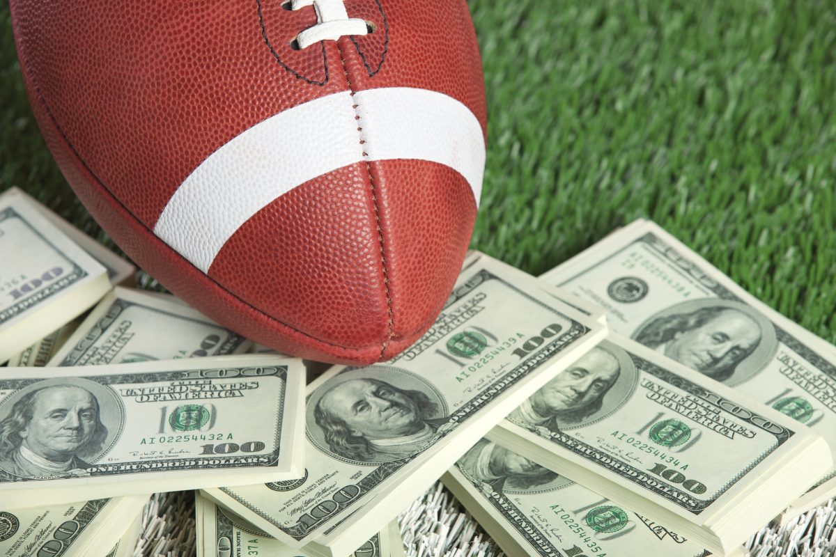 A college style football sits with a pile of money on a green field
